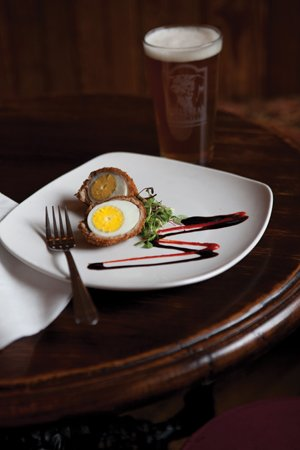 Bull's Head Public House: Scotch egg, hardboiled, coated with sausage and breadcrumbs, deep-fried and served with a balsamic reduction and Sriracha
